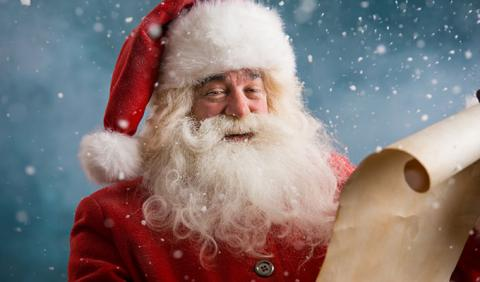 Santa Claus checking his holiday list of good girls and boys